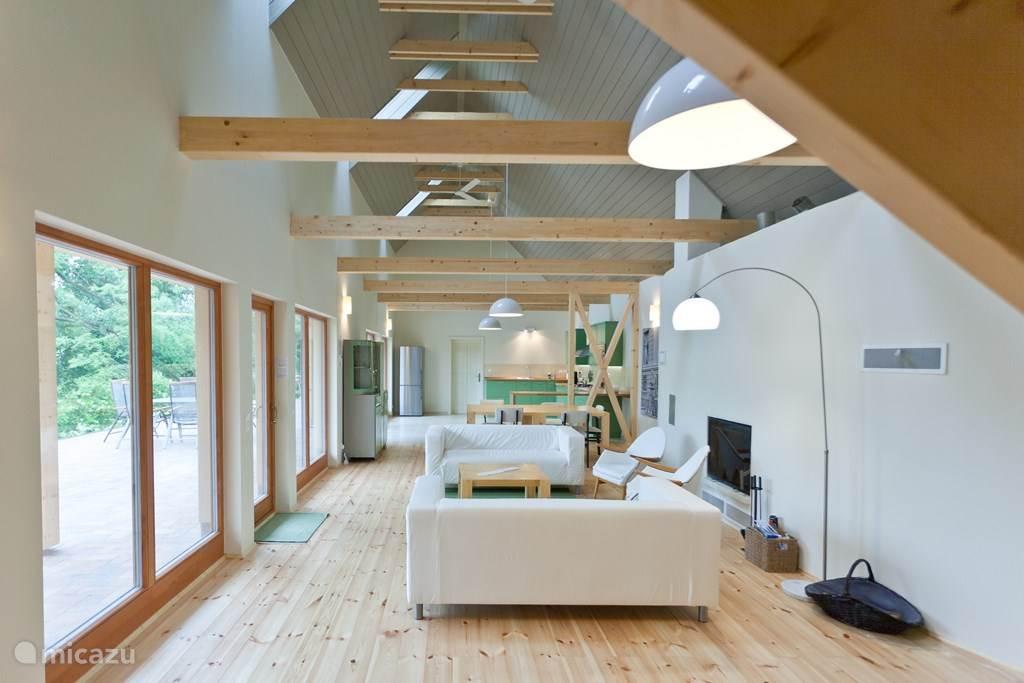 Vanuit de zeer ruime woonkamer kijkt u in de grote keuken. De ruimte kan worden verwarmd met een sfeervolle houtkachel en heeft een rustieke gezellige sfeer. De puien bieden een mooi uitzicht op terras en tuin.