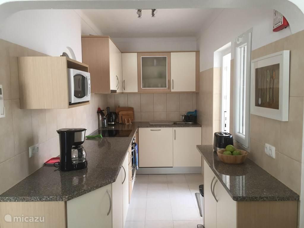 De zeer compleet uitgeruste moderne keuken met rechts de deur naar de patio met de wasruimte