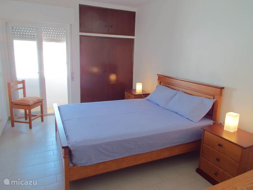 De ruime slaapkamer met tweepersoonsbed.