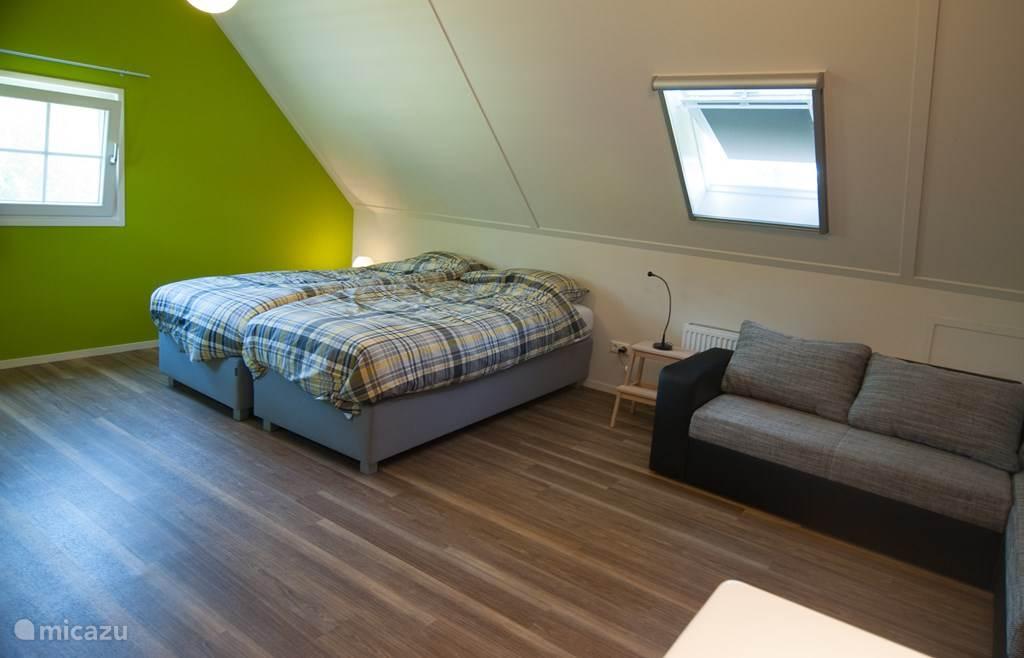 Woning Madelief: eerste verdieping, slaapkamer met twee boxspring bedden (90x210) en een grote wastafel, de bank is ook een slaapbank.