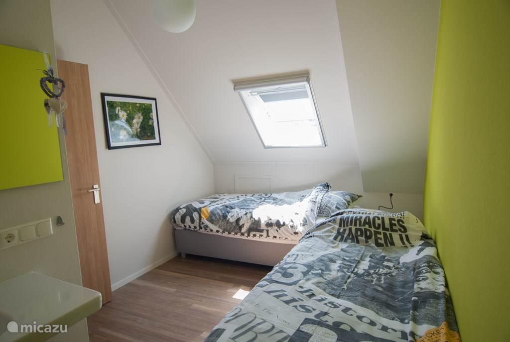 Woning Madelief: eerste verdieping, slaapkamer met twee boxspring bedden, (90 x210), en een grote wastafel.