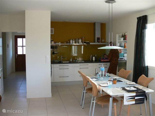 woonkamer en keuken in open verbinding. De keuken is zeer compleet. In de bijkeuken (de deur rechts) bevinden zich de electrische apparaten als afwasmachine, oven, wasmachine en droger. Ook is daar een 2e toilet.