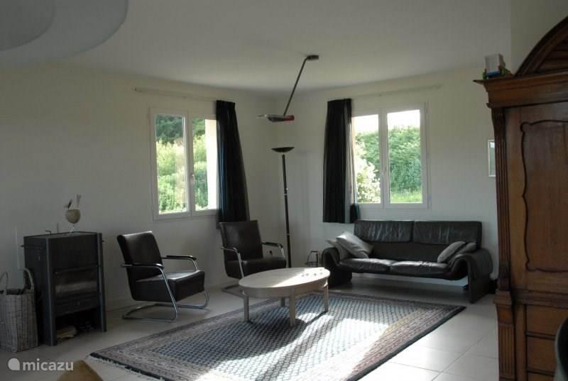HDe woonkamer beschikt over goed zittende stoelen, een bank. TV en muziekapparatuur. Er is een bibliotheek aan films en boeken.