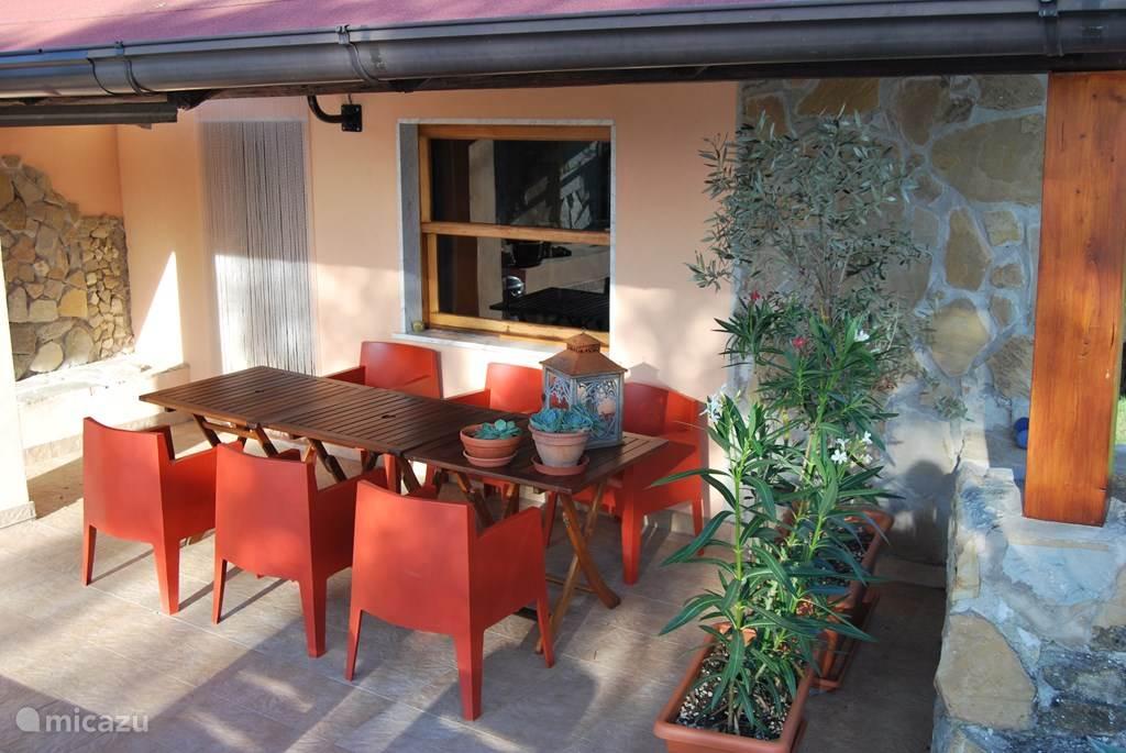 Het terras met eettafel voor 6 personen aan de voorkant van het huis.