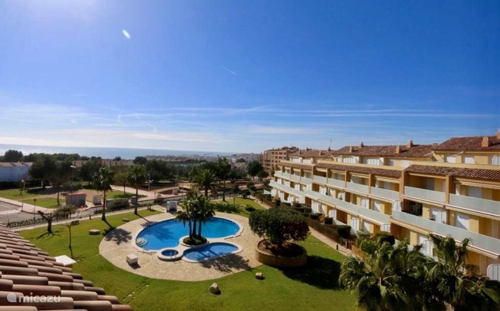 Uitzicht vanaf appartement op ligweide, zwembaden en zee