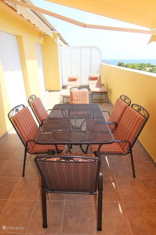 Een heerlijk beschut terras met volop privacy, 2 ligbedden en een eettafel met 6 stoelen
