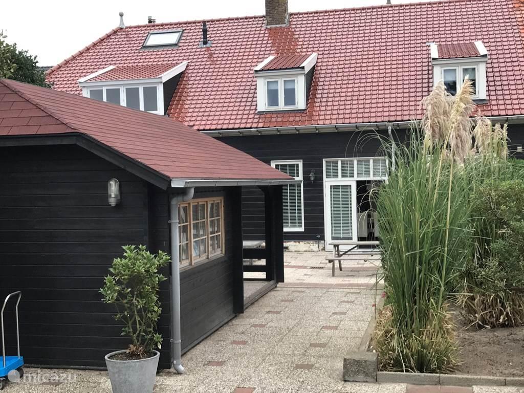 De achtertuin van de heerlijke woning in de Duinen van Huisduinen op steenworp afstand van het strand.