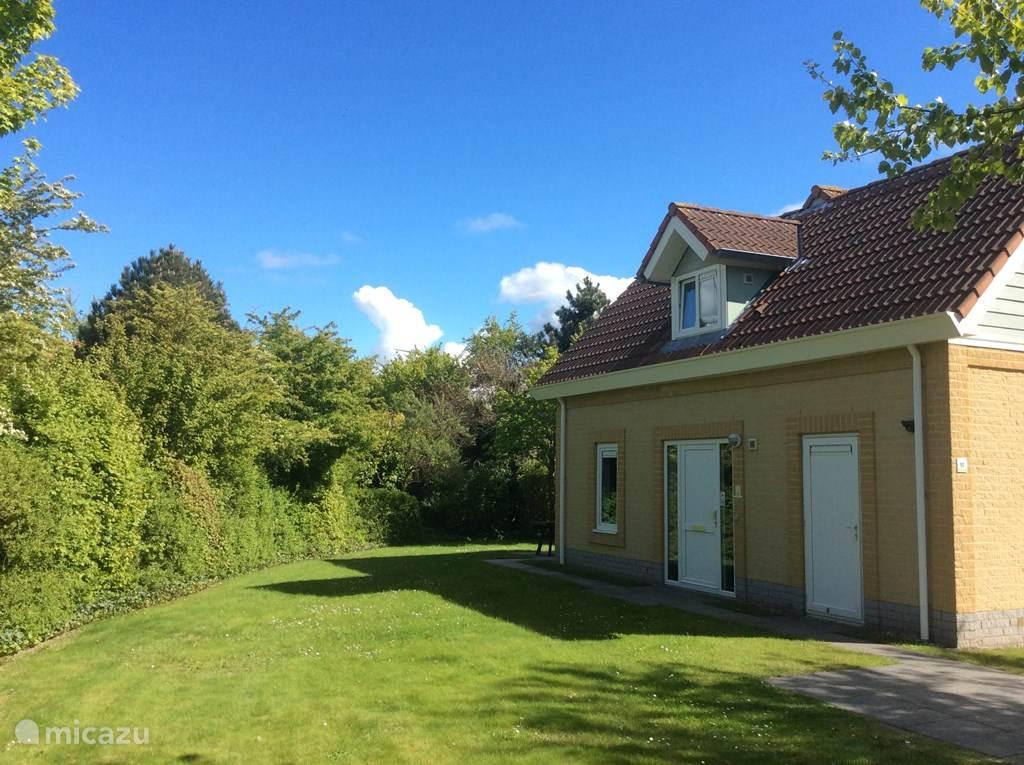Ruime tuin, met twee ligbedden en terrasset