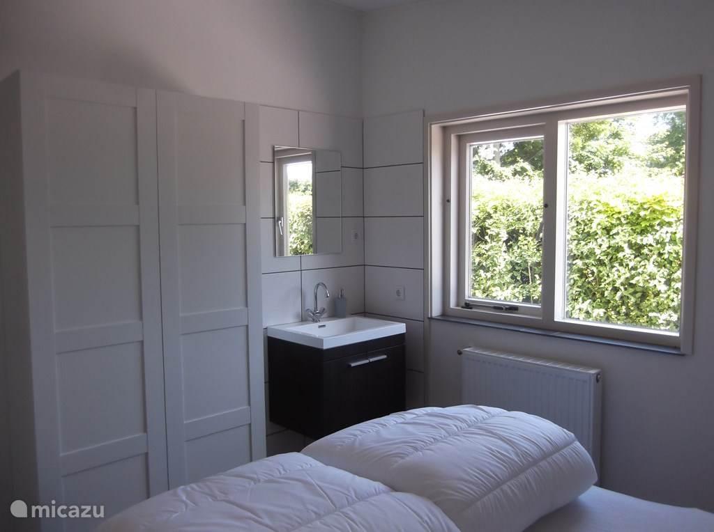 Slaapkamer voorzien van linnenkast en wastafel