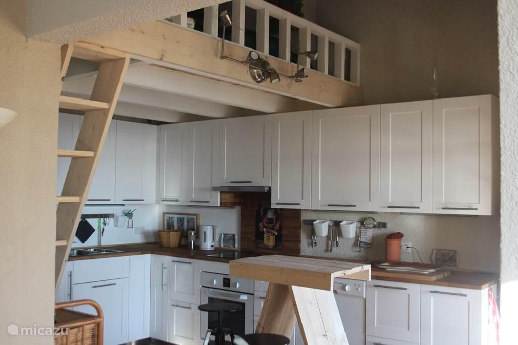 Keuken met daarboven de mezzanine gezien vanuit de woon-eetkamer
