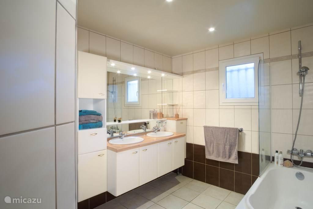 Badkamer met dubbele lavabo ligbad en toilet