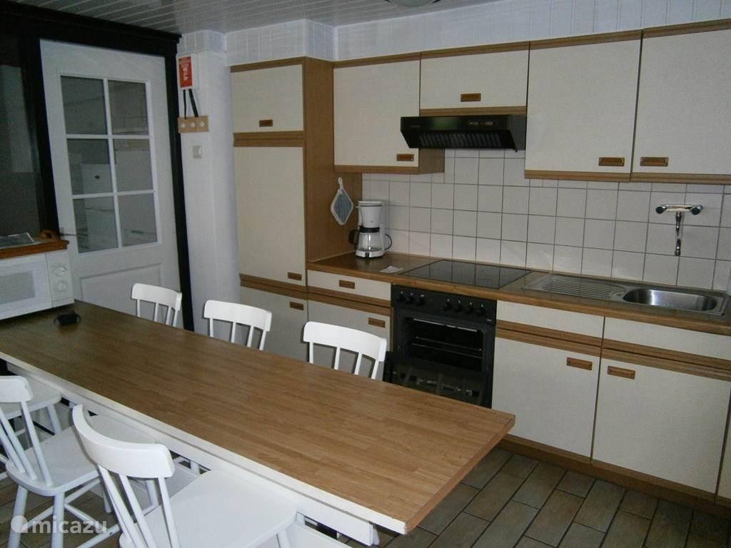 De keuken met tafel en 6 stoelen.