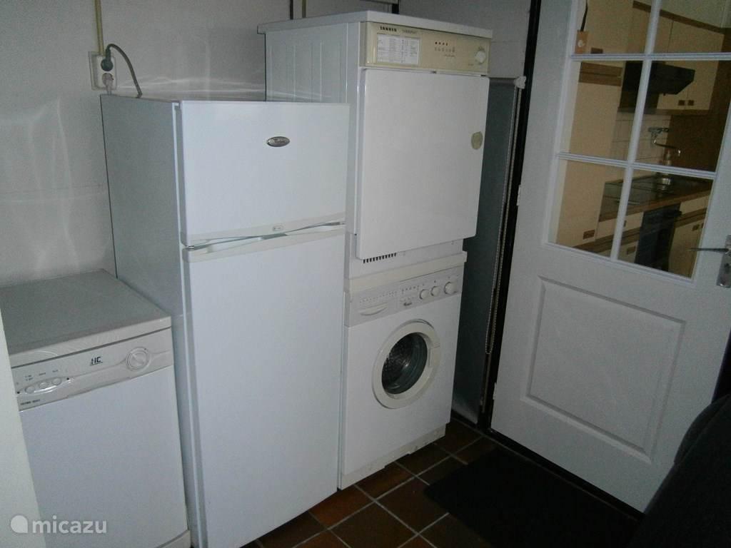 Je komt binnen in de berging, met wasmachine,droger,vaatwasser,koelkast met diepvriesvakje.