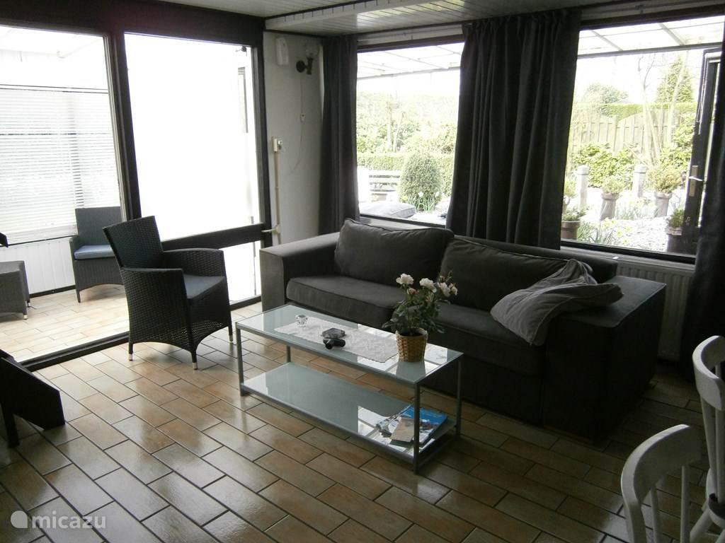 De kamer met 3 persoonsbank, salontafel en een fauteuil tv,dvd,op een tv meubel..