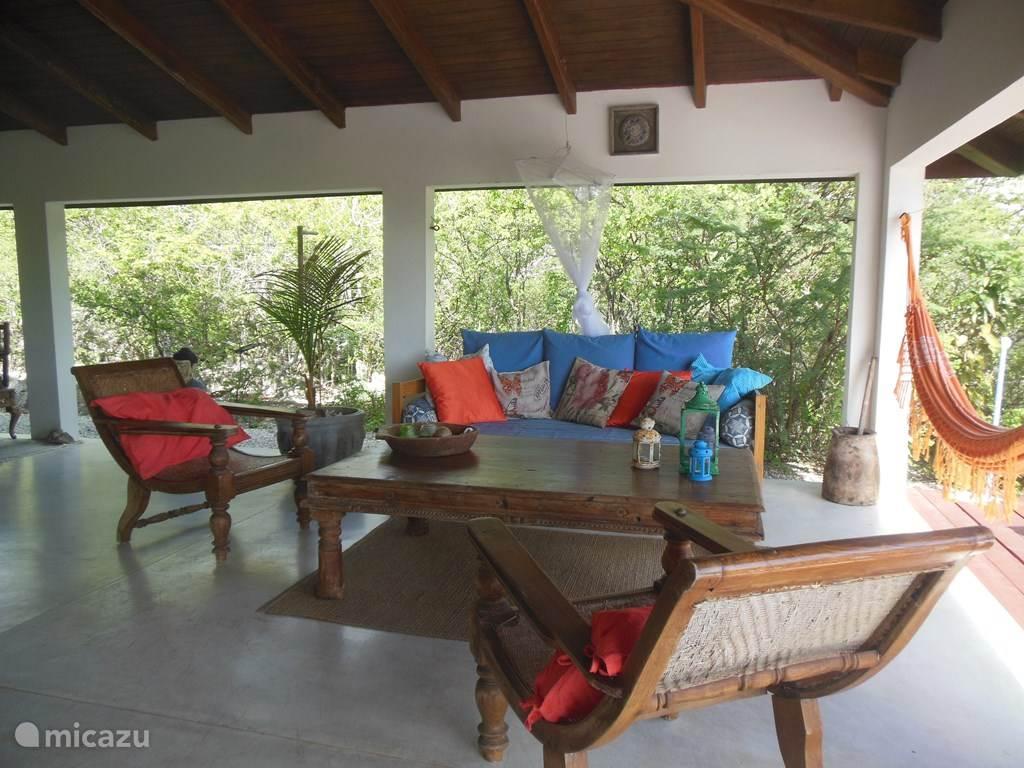 Ruime veranda met comfortabele bank hangmat en stoelen.
