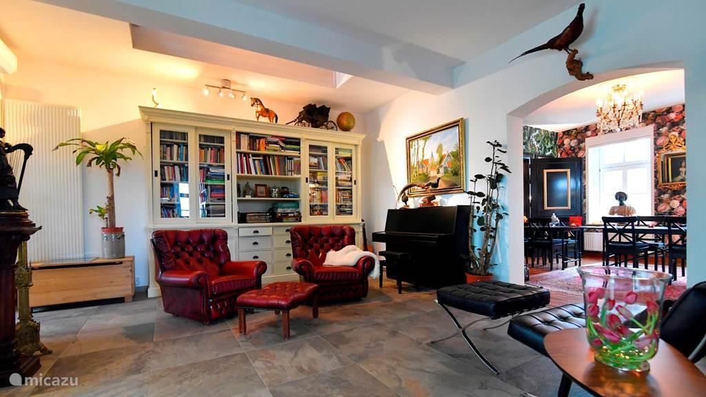 Zitgedeelte, naast de woon- en eetkamer met fauteuils, veel leesboeken en een piano