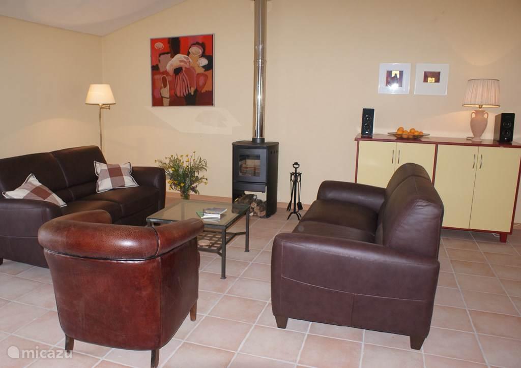 Sfeervolle ruime woonkamer met o.a. airco, TV (CanalDigitaal) en geweldige houtkachel.