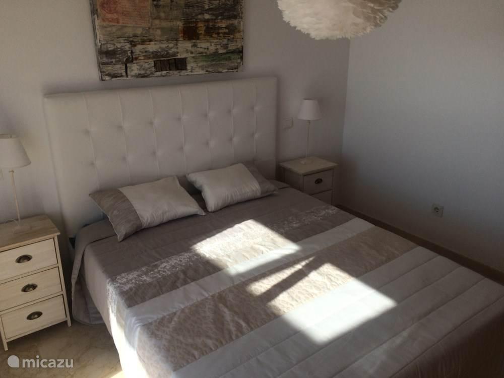 Masterbedroom met tweepersoons (180x200) bed en eigen badkamer. Grenzend aan terras met uitzicht op zee