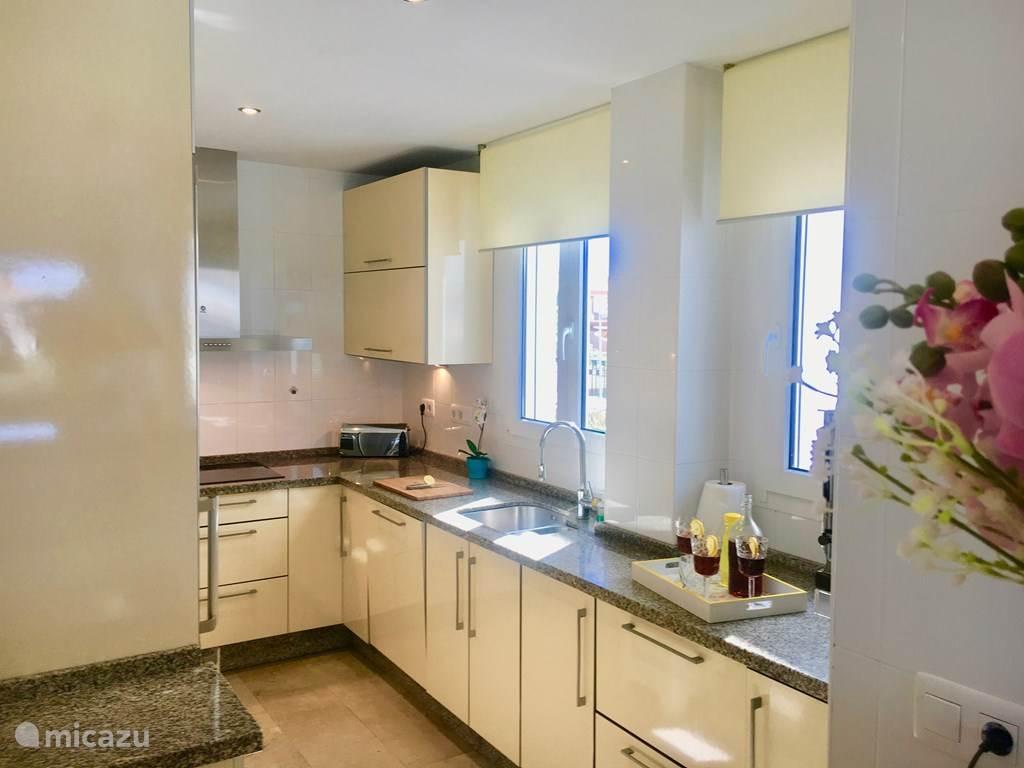 grote open en lichte keuken met alle  apparatuur en uitgebreide keukengerei