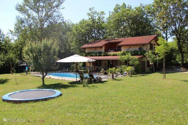 Gitegebouw met zwembad, trampoline en tuin.