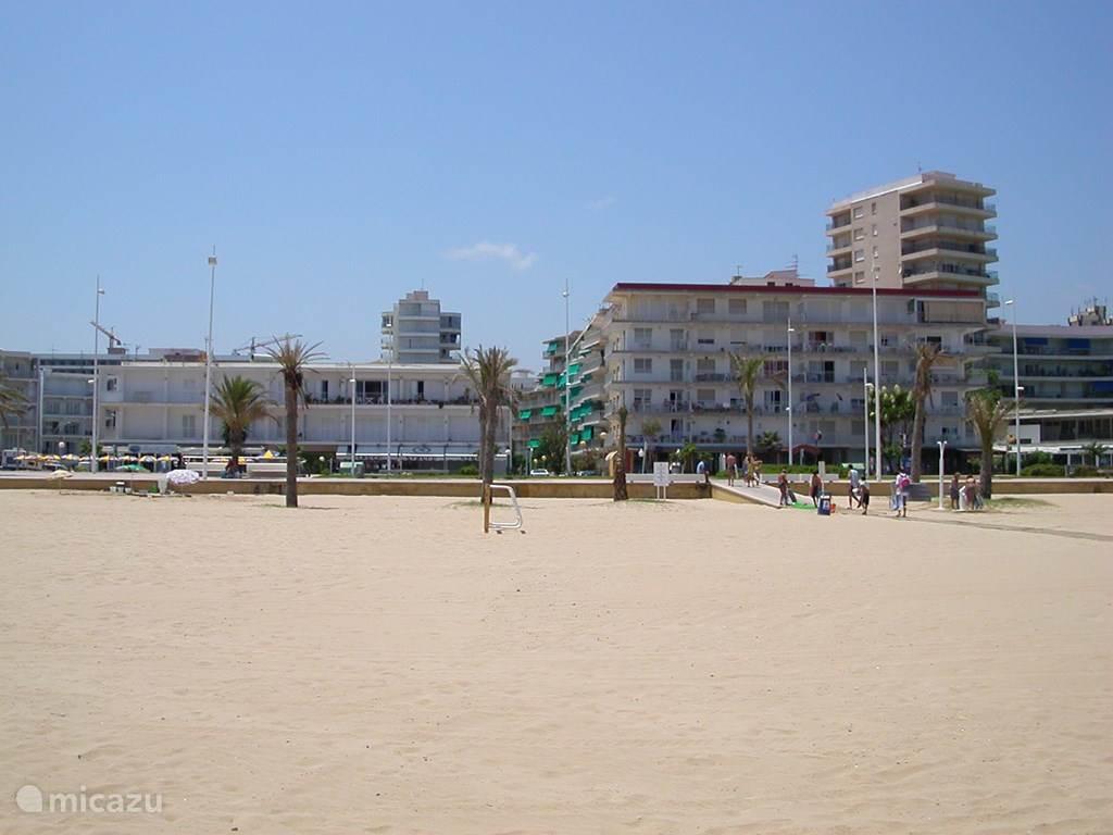 Het mooie zandstrand met op de achtergrond het appartementen complex. Vanuit het straatje loop je zo het strand op met douches en houten vlonders vrijwel tot aan de zee.
