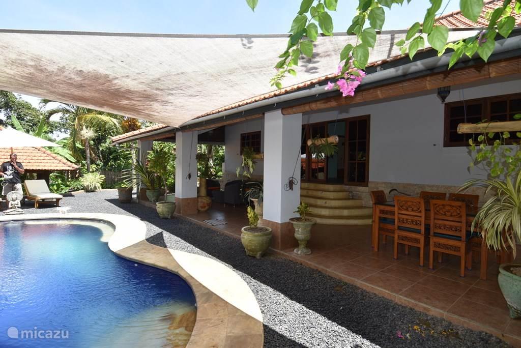 de veranda met launch sofa en eettafel direct naast het zwembad