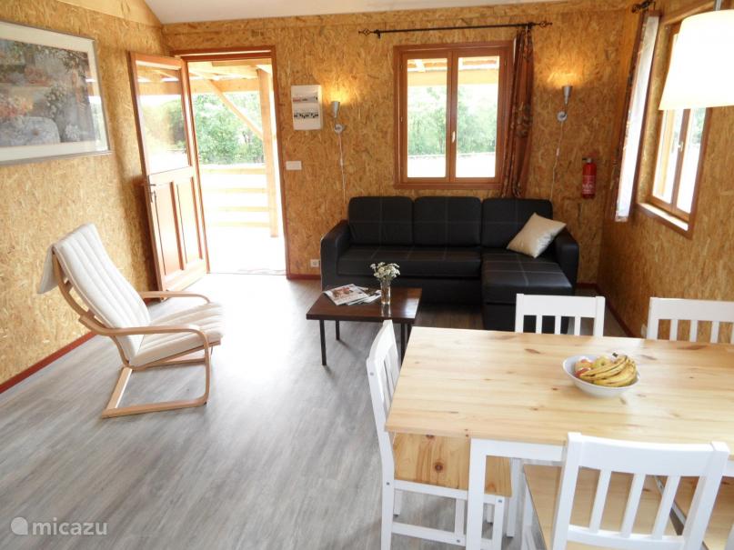De leefruimte is voorzien van een comfortabele zitbank met handig tafeltje en een eettafel voor 5 personen.