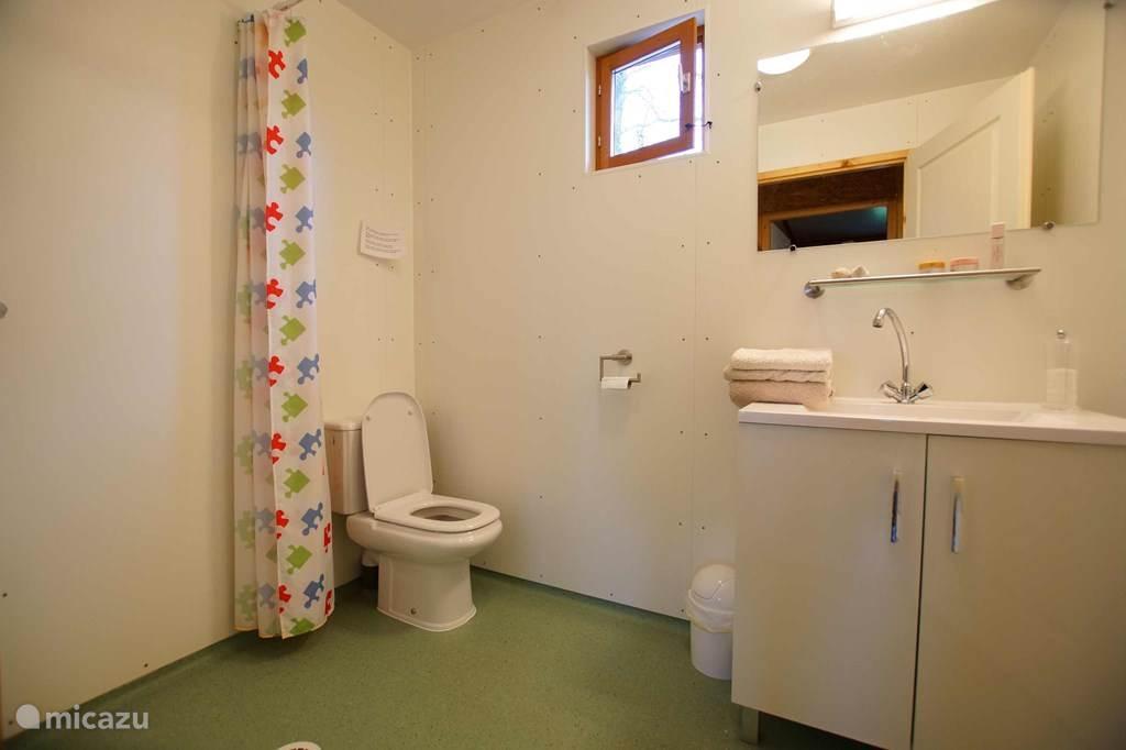Elk chalet is voorzien van een eigen badkamer met alle comfort. Wastafel met spiegel en kast, douche en toilet. Het raam is voorzien van een muggengaas zodat U het steeds kunt openlaten en tijdens de winterperiode is de badkamer voorzien van een elektrische verwarming.