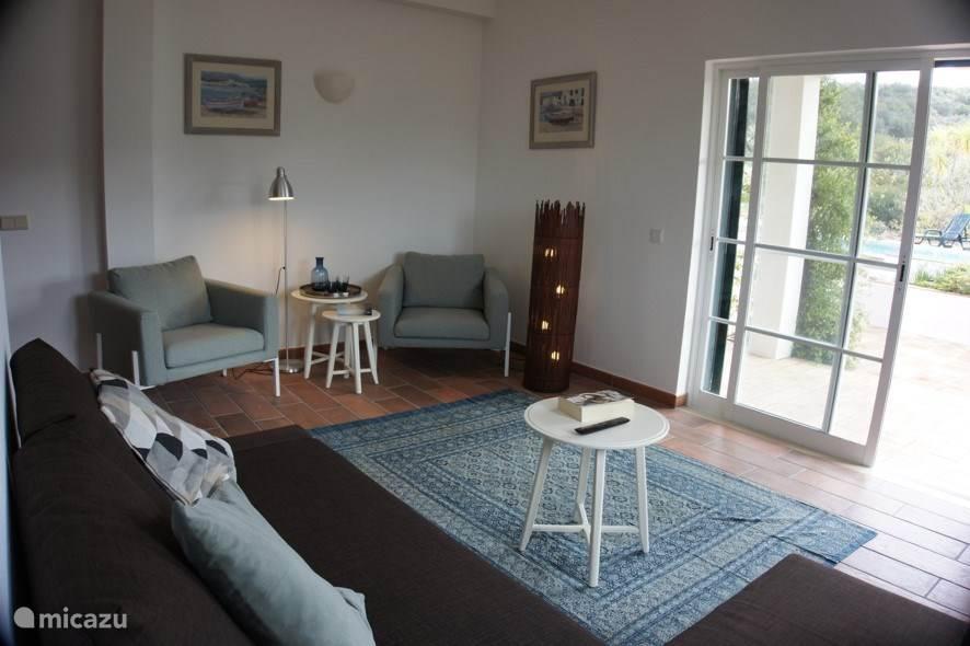 De woonkamer biedt ruimte aan zes gasten en is zowel voor de zomer- als wintermaanden comfortabel ingericht. Vanuit de woonkamer kun je via openslaande deuren naar de veranda.