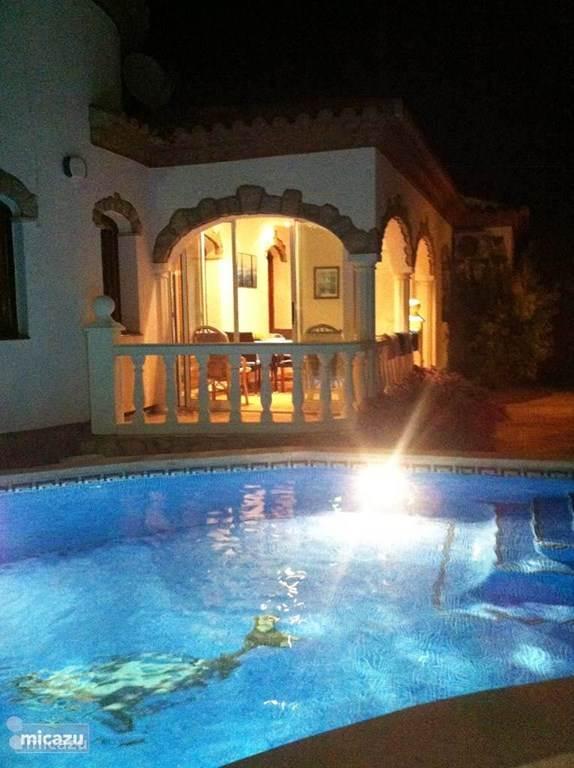 Zwembad en serre in het donker.