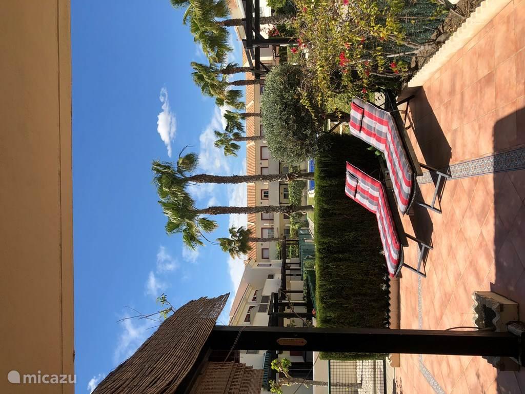 Uitzicht vanaf het terras op de gemeenschappelijke tuin met groot zwembad