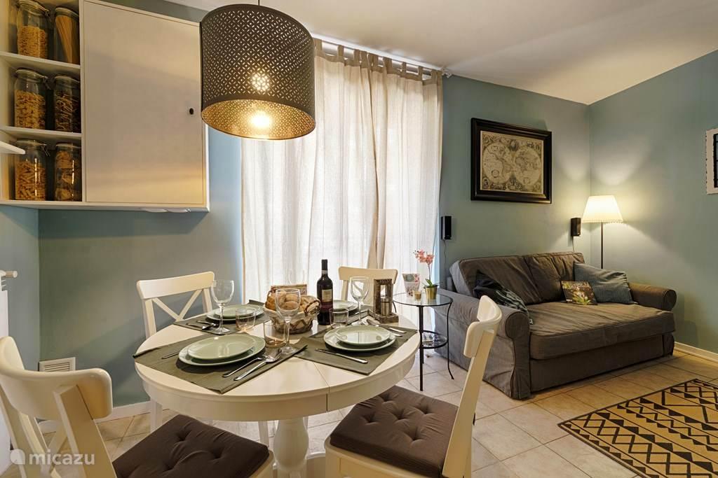 De gezellige woonkamer met comfortable slaapbank, eettafel en tv meubel