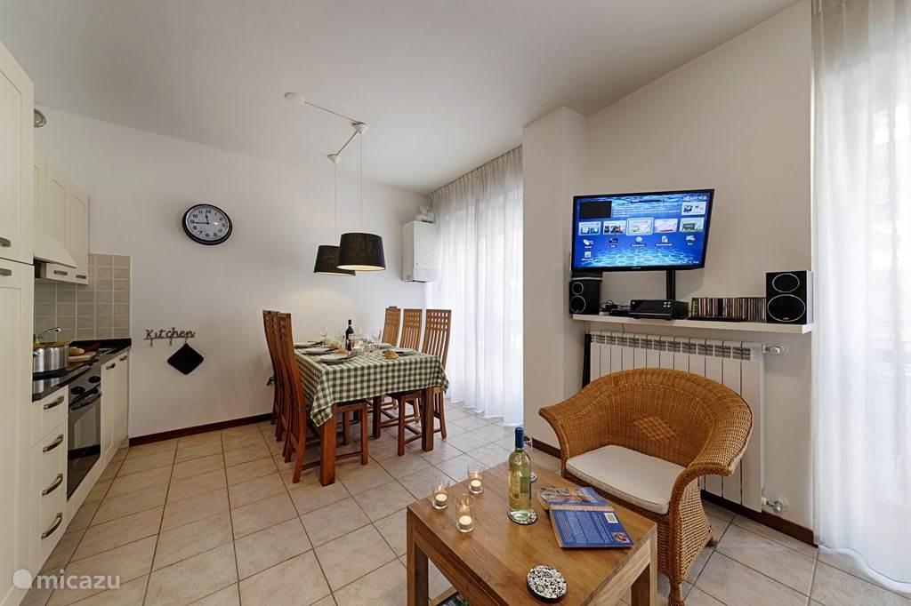 De woonkamer en keuken met eettafel