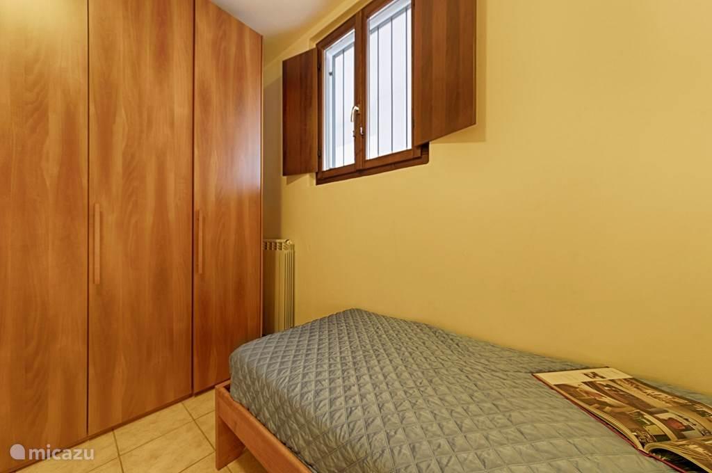 De kleine slaapkamer met ruime kledingkast.