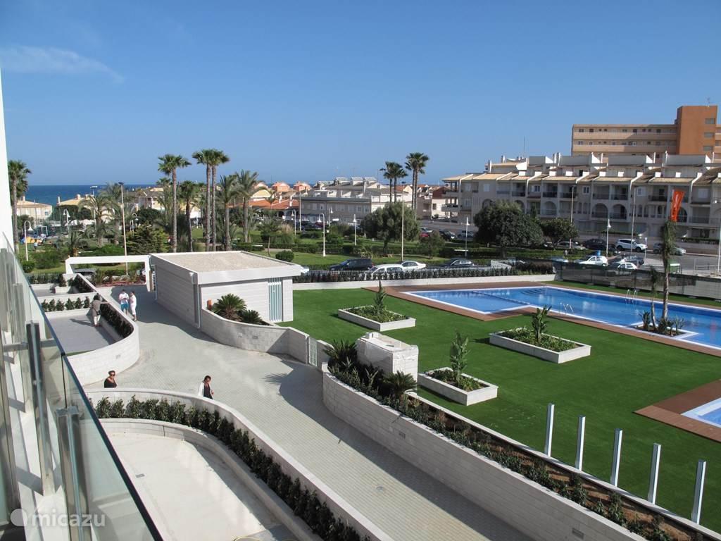 Uitzicht vanaf het balkon: het zwembad en de zee.