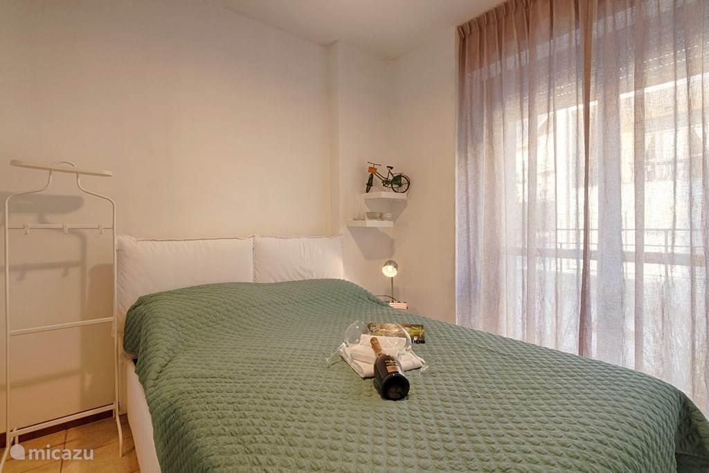 De slaapkamer met tweepersoonsbed, plafondventilator en grote kledingkast.