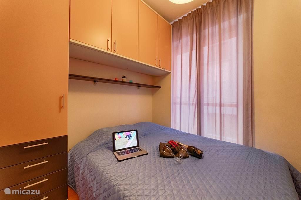 De grote slaapkamer met tweepersoonsbed en ruime kledingkast.
