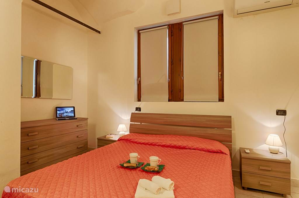 De slaapkamer met tweepersoonsbed en grote kledingkast.