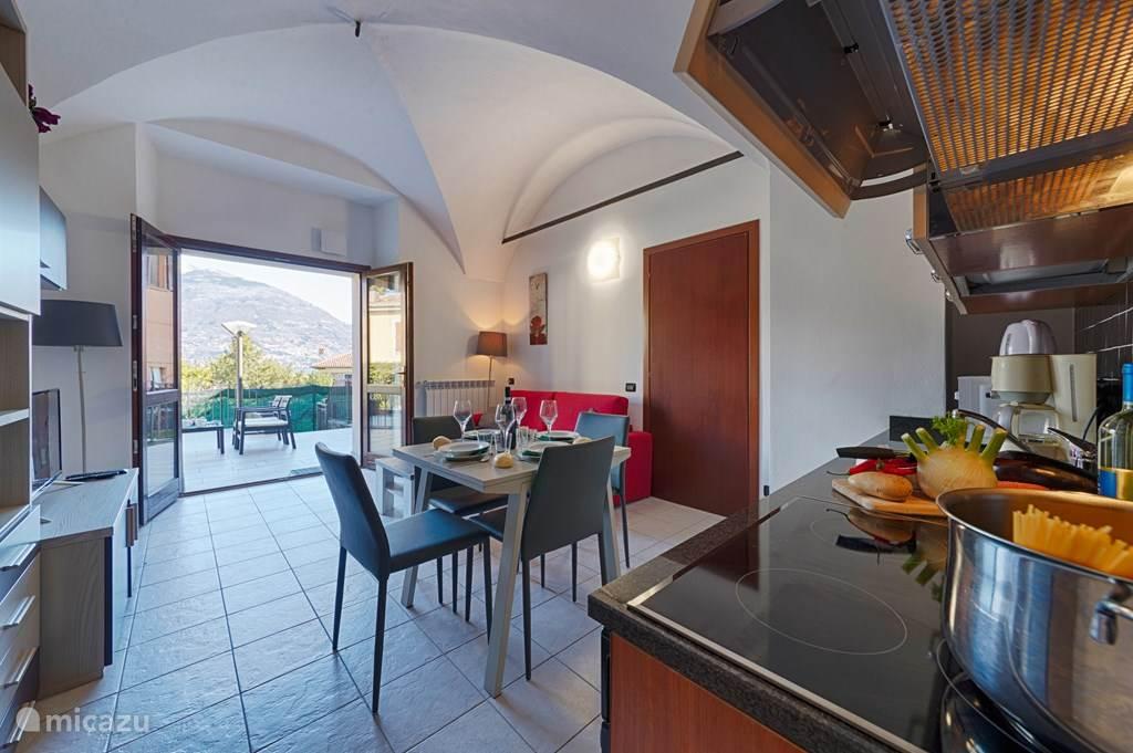 De keuken, woonkamer en aangrenzende betegeld zonneterras.
