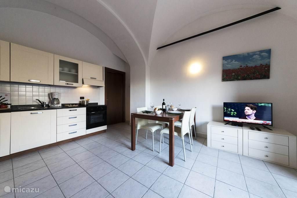 De keuken, eettafel en woonkamer.