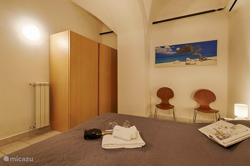 De slaapkamer met twee-persoonsbed en grote kledingkast.