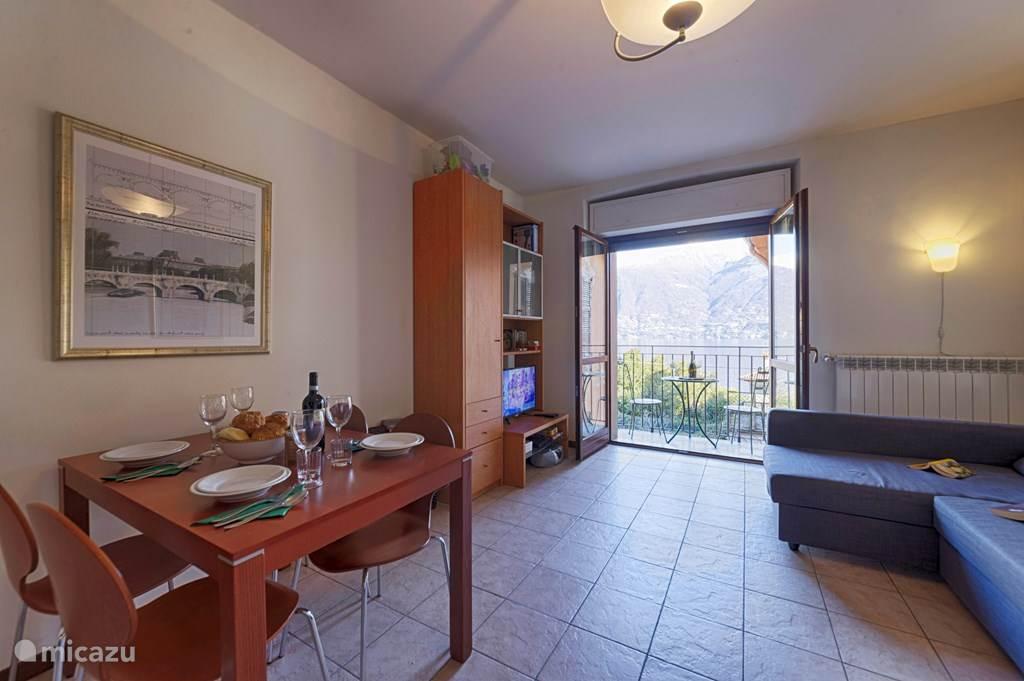 De woonkamer met eettafel, twee-persoons slaapbank en prachtig uitzicht vanaf het aangrenzende Franse balkon.
