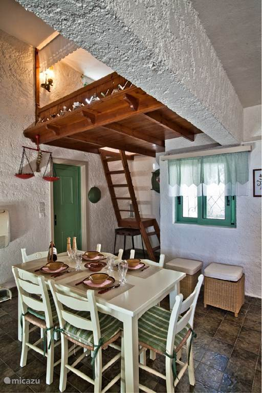 The kitchen with a traditional double open loft bed above.
