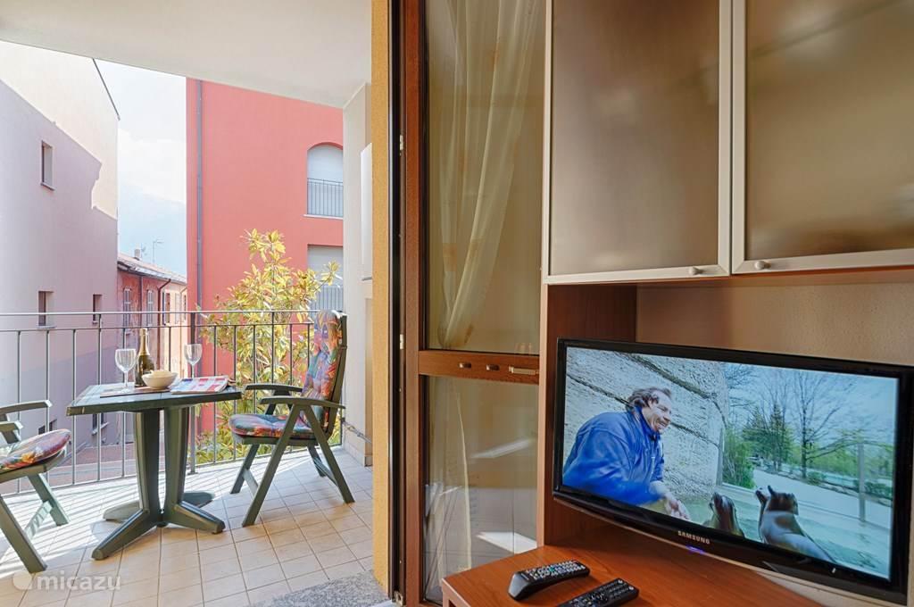 De tv kast en het aangrenzende overdekte balkon.