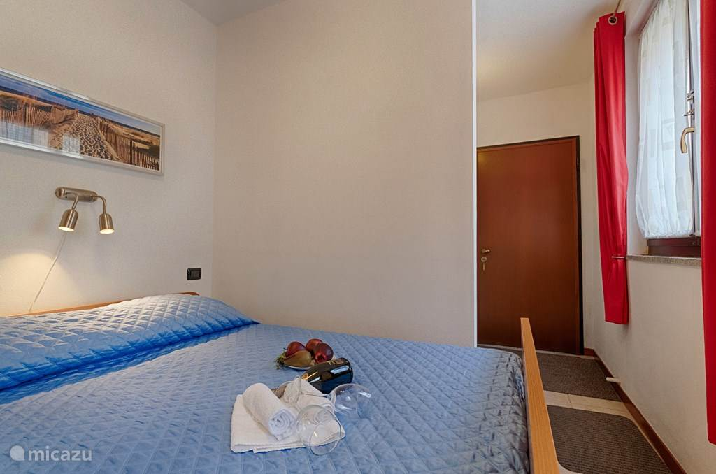 Tweepersoonsbed in het voorportaal van het appartement.