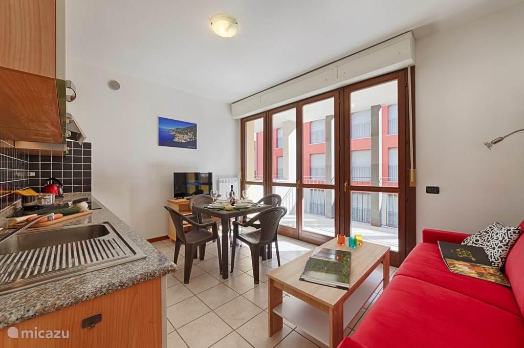 De woonkamer met het aangrenzende ruime overdekte balkon.