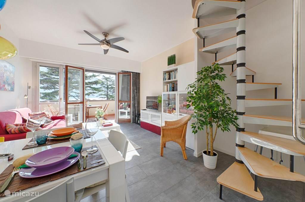 De moderne, frisse, woonkamer met het aangrenzende ruime balkon.