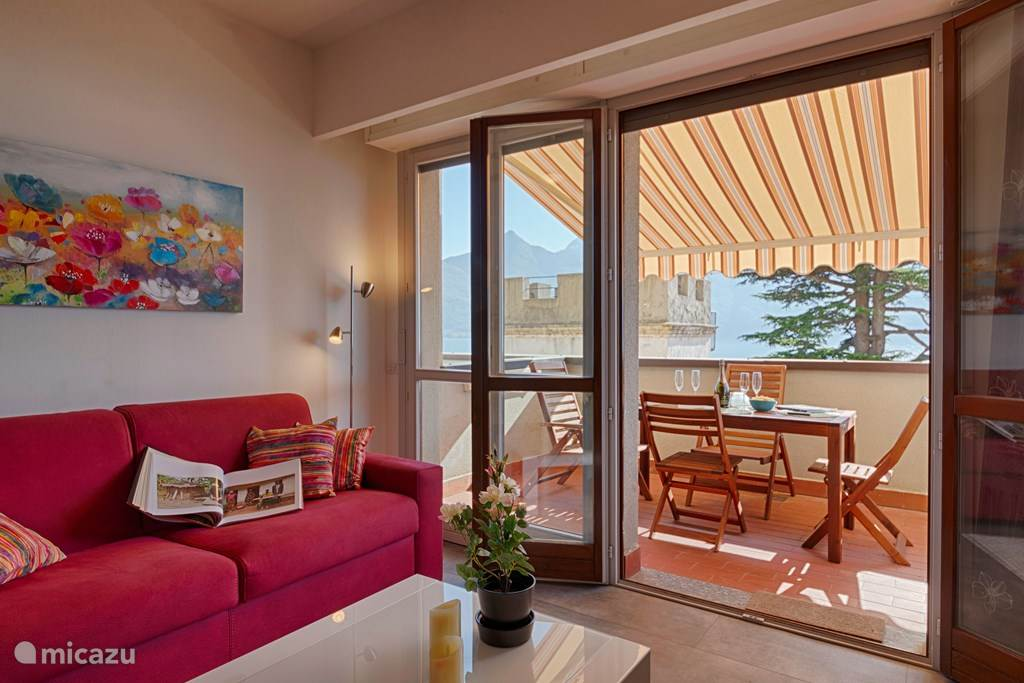 De woonkamer met het aangrenzende balkon met zonnewering.