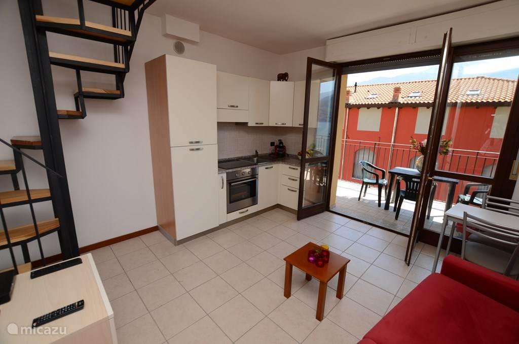 De woonkamer met de keuken.