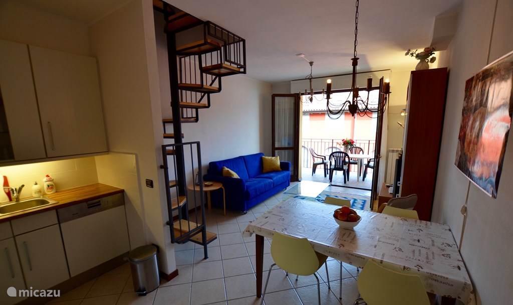 Keuken, de woonkamer en de wenteltrap naar de bovenverdieping.